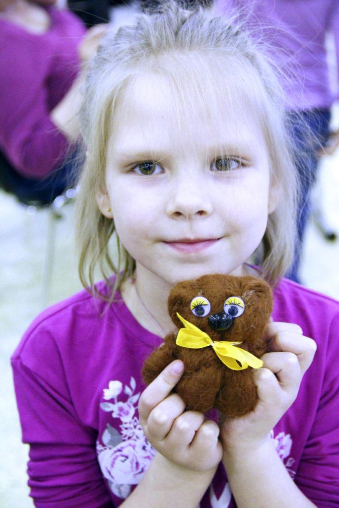 Девочка держит поделку из шерсти